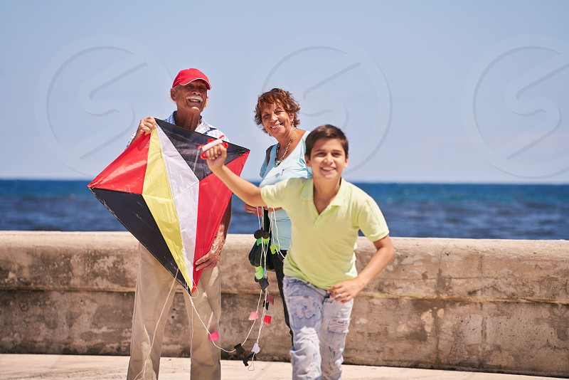 Happy tourist family on holidays in Cuba. Hispanic grandpa grandma and grandson having fun near the sea. Boy and grandparents running and playing with kite  photo