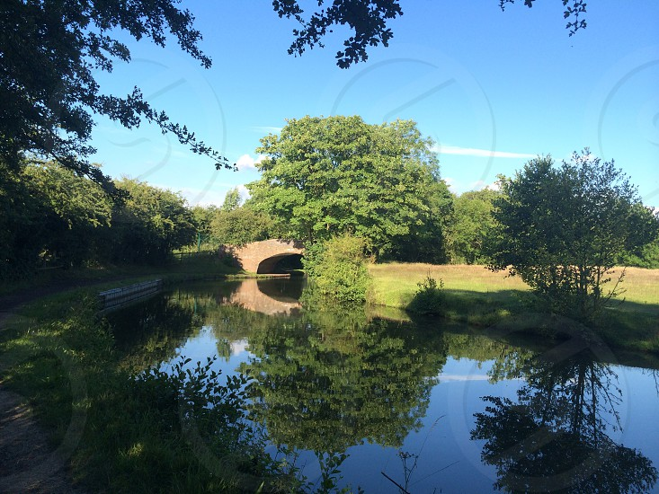 Canal bridge overpass hill grass outdoor trees bushes water Sky clear reflection calm sunny sun photo