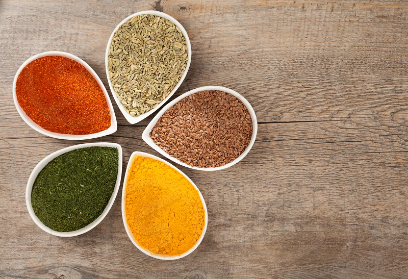 Fresh Spices in bowls over a wooden background photo