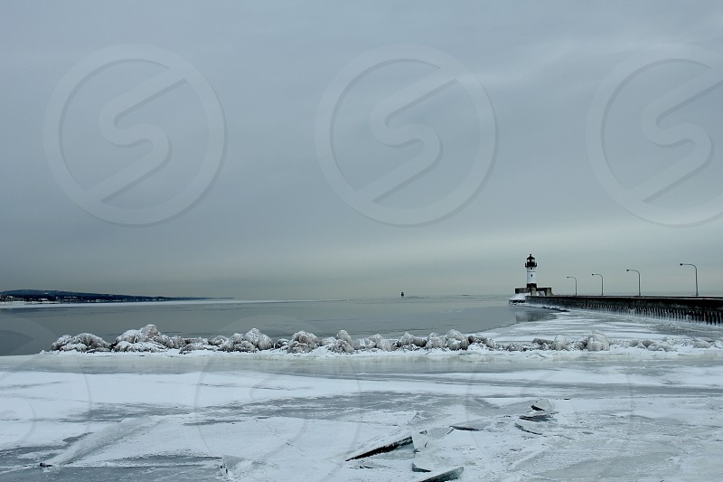 Winter in Duluth MN. Lighthouse stretches out on the icy cold water in the evening photo