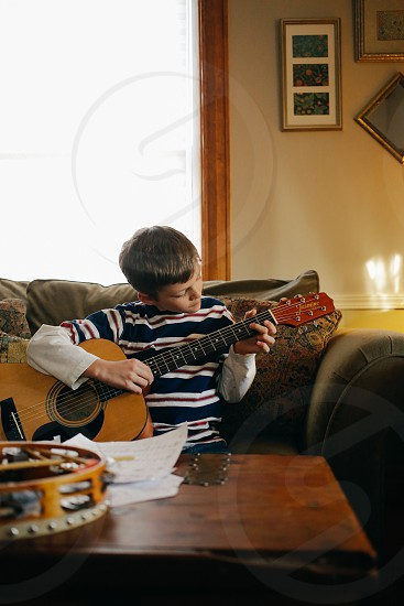 child in blue and white striped long sleeves shirt playing a guitar photo