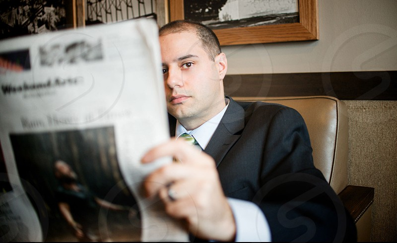 man wearing black suit reading newspaper photo