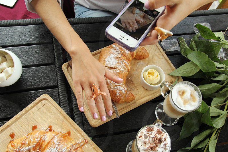 Phone media picture taking breakfast food eat sweet dessert latte coffee butter cozy bright girl hands nail croissant wooden background photo