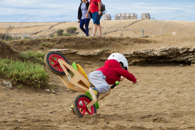 Boy in red jacket falling from bike on the sand beach  photo
