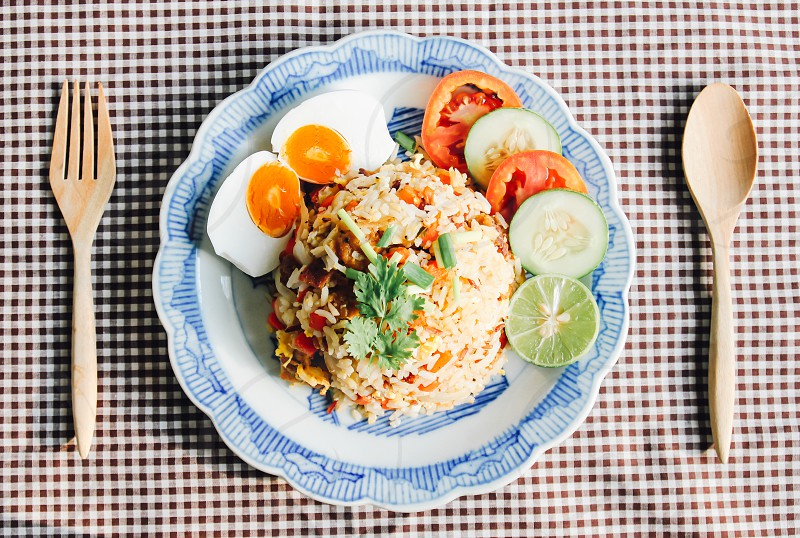 Delicious Thai fried rice with wooden spoon on tablecloth photo