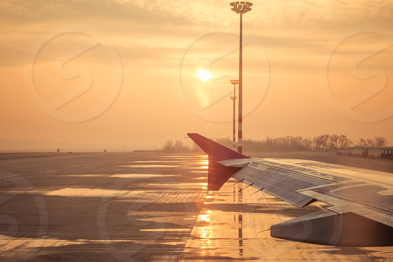 Airport And Airplane Wing At Sunset photo
