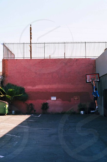 man in blue t shirt holding basketball ring beside red concrete wall photo