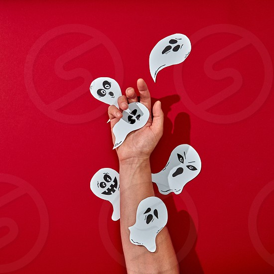 Paper handcraft work various ghosts decorate the hand of a man on a red background with space for text. Halloween creative composition. Flat lay photo