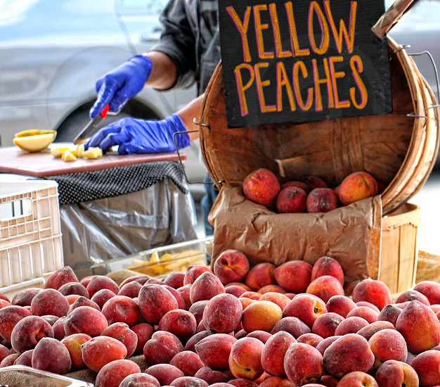 Yellow peaches in a basket sold at a farmer's market photo