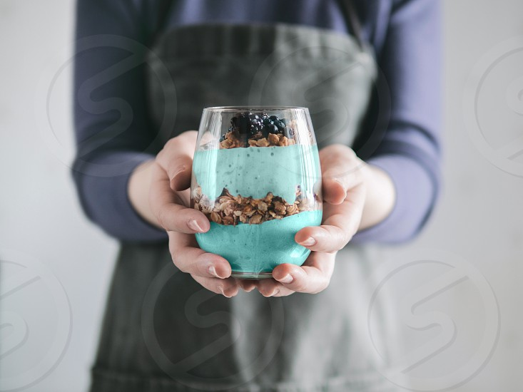 Triffle dessert in woman hands. Blue spirulina and fruit smoothie with granola blueberry and blackberry in glass. Healthy detox food and breakfast idea and recipe. photo
