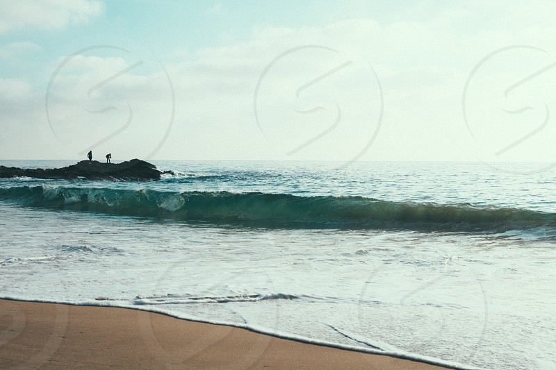 sea waves crashing on beach shore under white clouds and blue sky during daytime photo