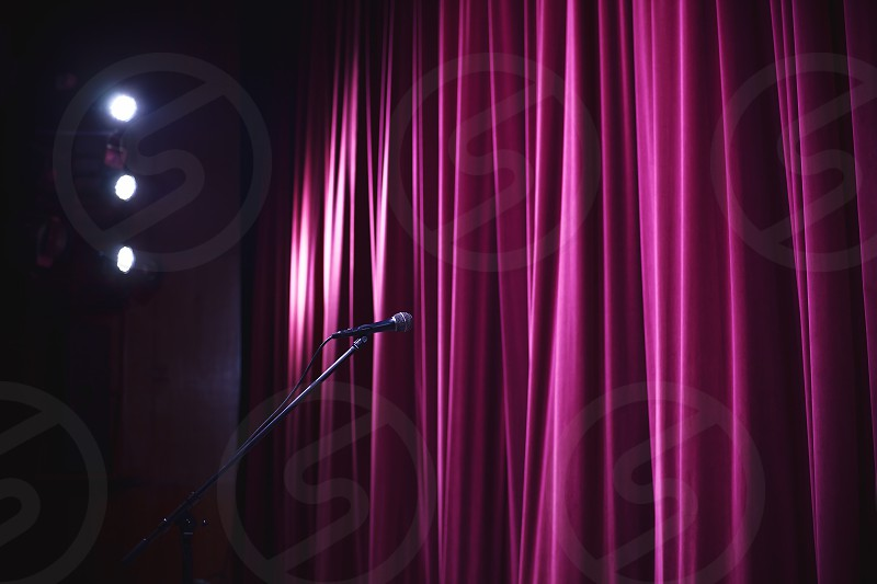 Ready for performance closed stage with big decorative curtain microphone on stand in front of it and big lighting equipment in corner. photo