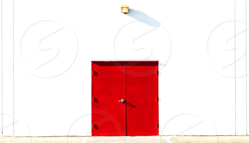 Double red doors on a white wall in an industrial area. photo