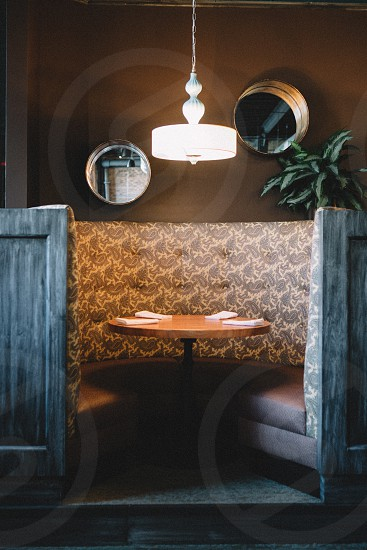 cafe with brown enclose sofa and table under white hanging lamp photo