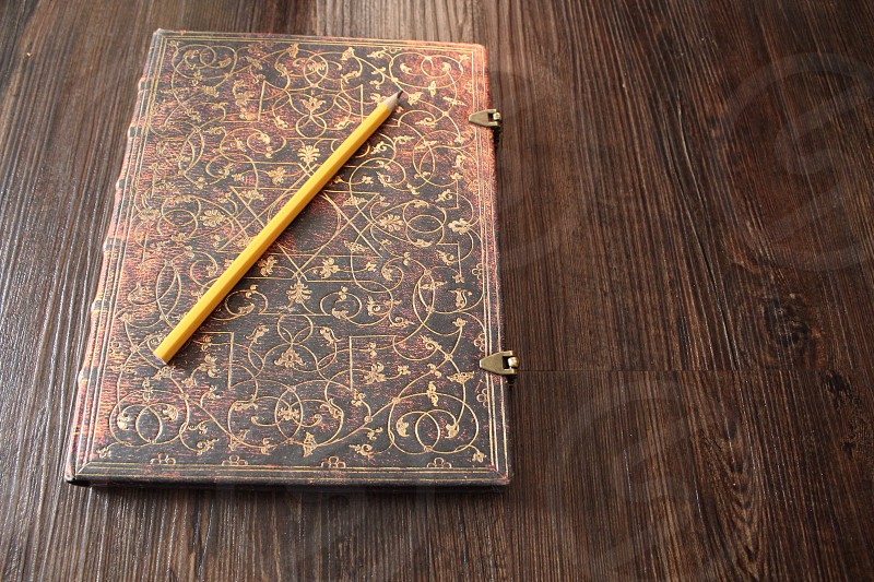 yellow wooden pencil on brown and black hardbound book photo
