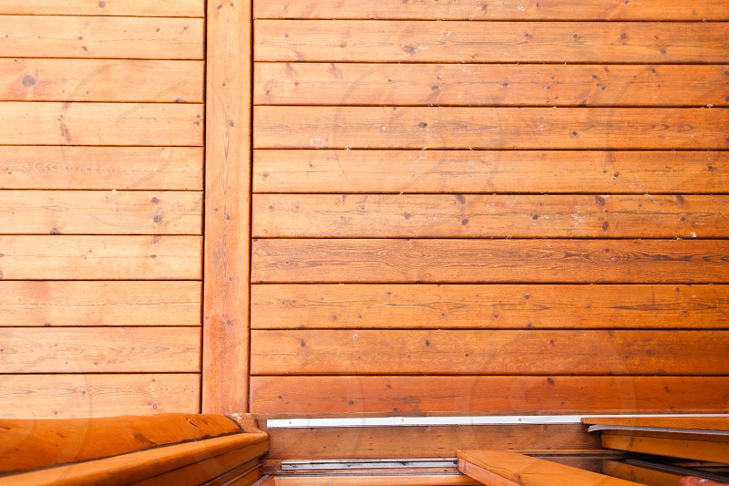 Open glass door leading onto wooden deck or porch from straight above with rich warm wood grain textures and colors photo