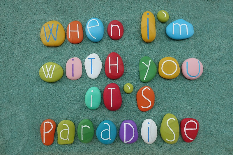 When I'm with you it's paradise love message composed with multi colored sea stones over green sand                      photo