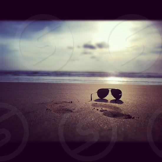 black aviator sunglasses on brown sand photo