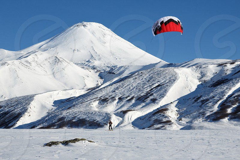 KAMCHATKA AVACHA VOLCANO RUSSIA - NOVEMBER 22 2014: Snowkiting or kiteboarding - sportsman glides on skis on snow on a background of active Avachinsky Volcano (Avacha Volcano) on sunny day. photo