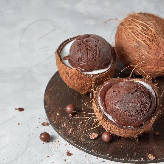Two halves of coconut with homemade chocolate dessert on a wooden board on a gray background with copy space.. Summer concept. photo