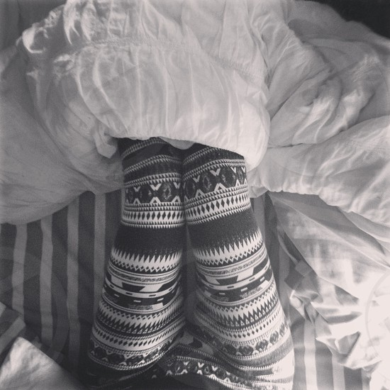 grayscale photography of woman in aztec print leggings laying down on bed covered with white blanket photo