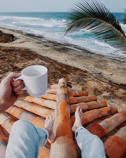 man in blue jeans and bare feet sitting on a clay curved tile roof on a beach holding a white coffee mug by a palm tree photo