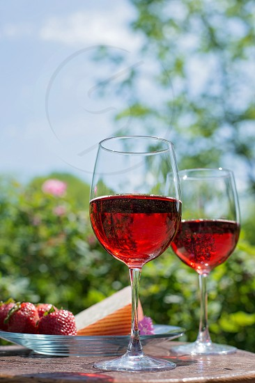 wine rose' pink outdoor natural light dining strawberries cheese rustic glasses for two photo