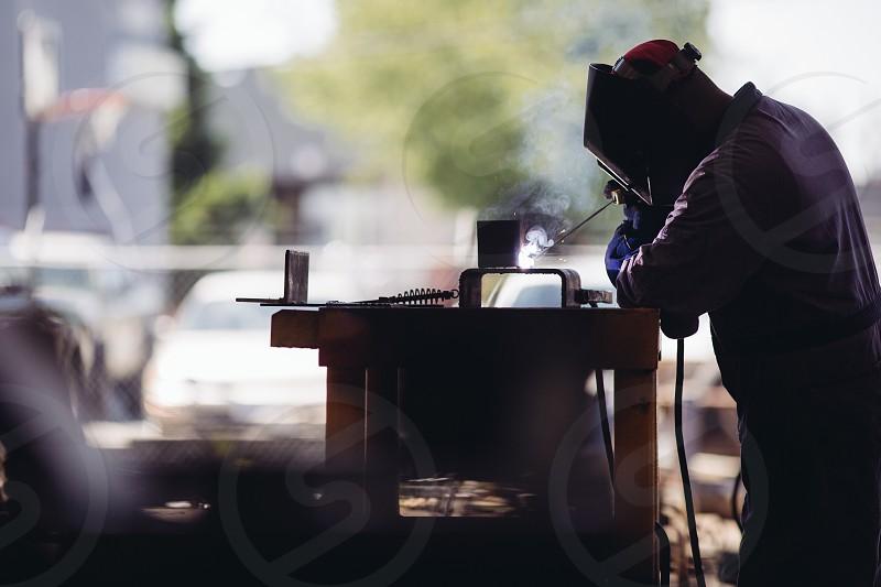 man in grey arc welding grey steel frame on yellow bench photo