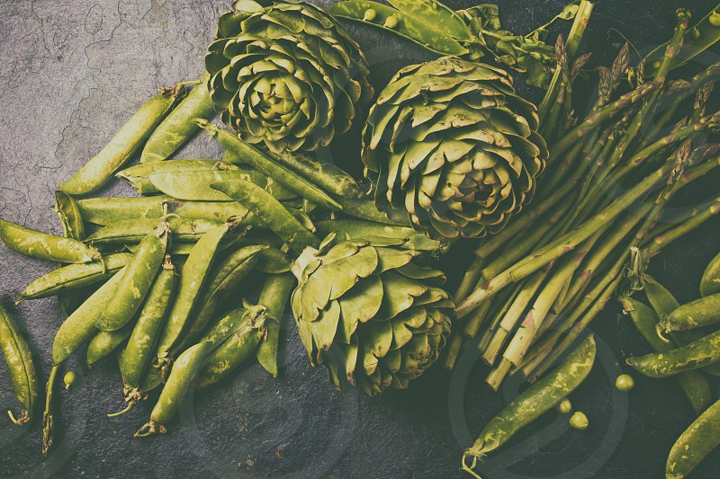 food background with fresh green vegetables - asparagus artichoke and green pea. Toned photo. photo