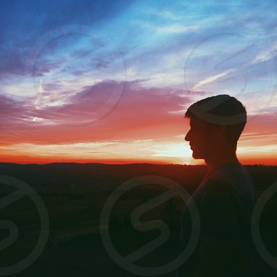 man in grey t shirt watching sunset photo