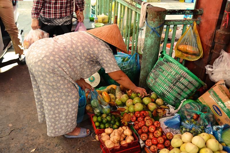 Lady selecting fruit market Ho Chi Minh City Vietnam photo