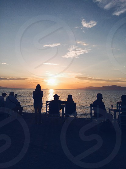 silhouette photography of group of people facing sea and sunset photo