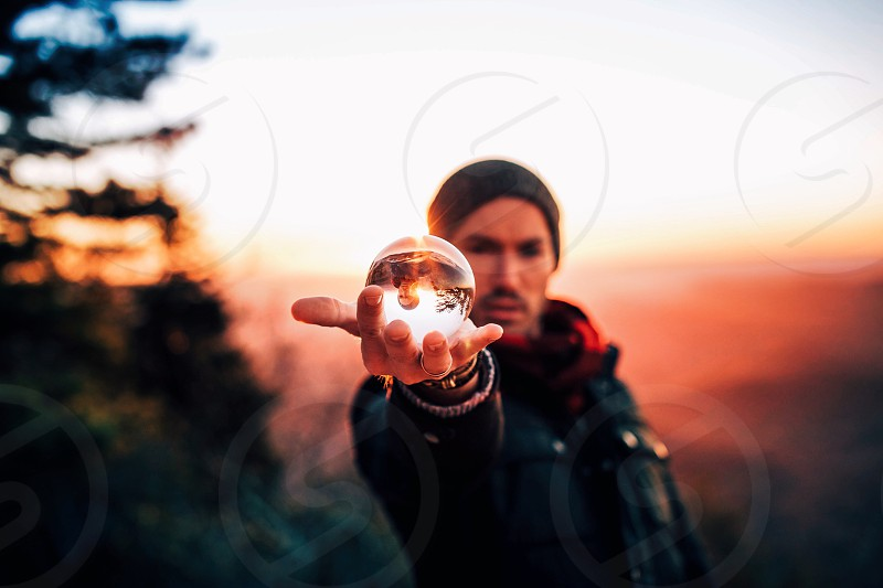 focus photography of round clear glass ball on the palm of man wearing black leather jacket and black knit cap during daytime photo