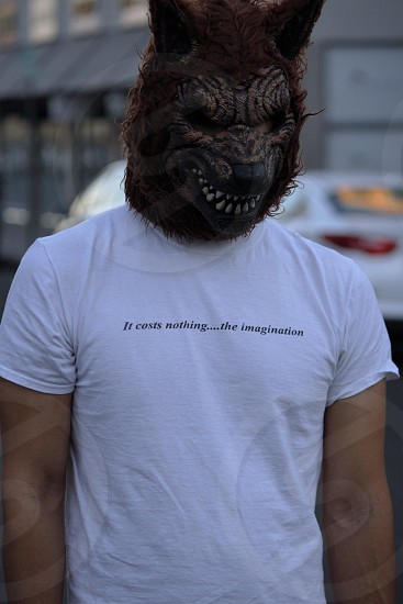 man wearing black it costs nothing the imagination printed white t shirt and werewolf mask walking on the street with white cars behind him photo