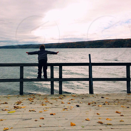 boy in blue jacket and black pants standing on gray wooden hand railings near the sea photo