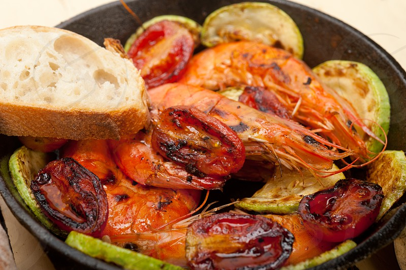 roasted shrimps on cast iron skillet  with zucchini and tomatoes photo