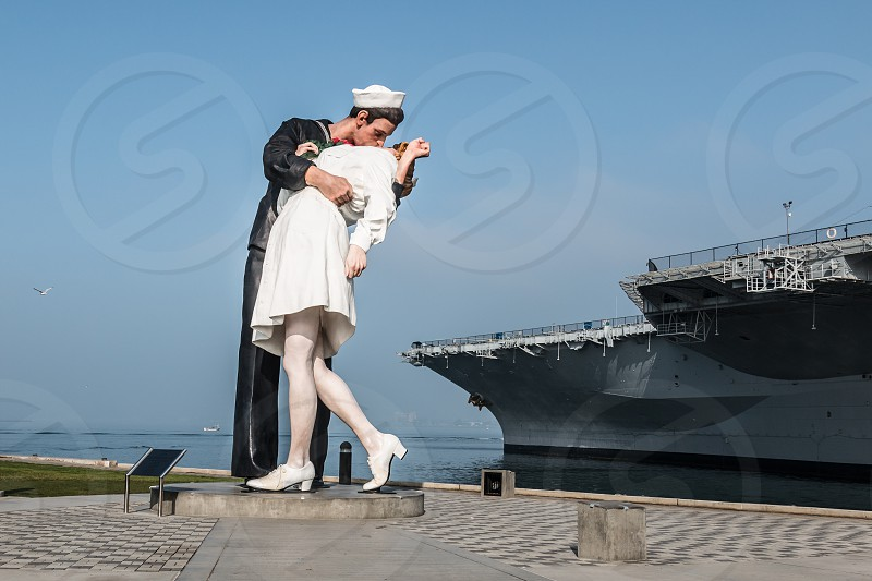 Statue in San Diego California commemorating the iconic V-J photo of a sailor kissing a nurse at the end of World War II with the USS Midway museum. photo