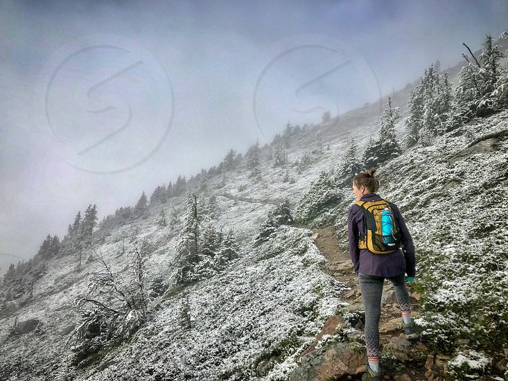 Woman Hiking in narrow trail with light snow photo