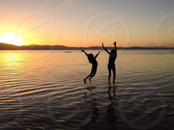 Children happy outdoors playing water lake sunset  photo