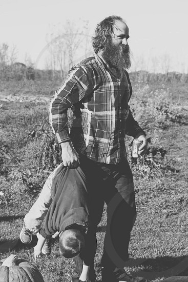 man wearing plaid long sleeved shirt carrying boy with right hand photo