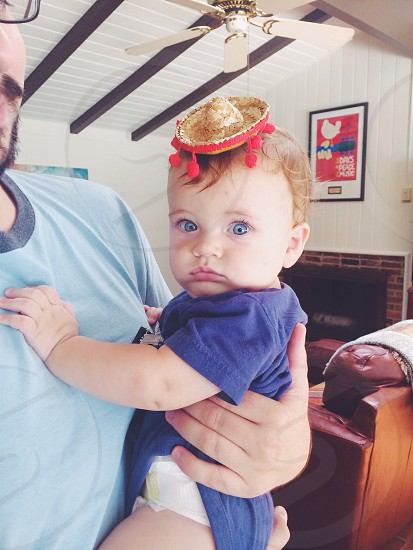 Baby wearing sombrero with big blue eyes looking at the camera being held by a man.  photo