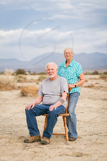 An Elderly Man and Woman pose for a portrait in a desert field on a cloudy day photo