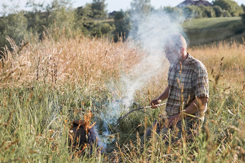Man sitting in a grass beside a campfire on a meadow. Candid people real moments authentic situations photo