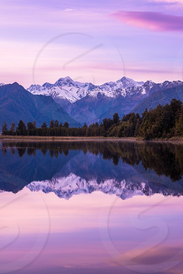 A beautiful sunrise above Lake Matheson with the Southern Alps in the background photo