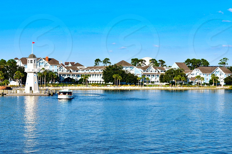 Orlando Florida. February 09 2019. Taxi boat sailing on lake with background of villas and lighthouse at Lake Buena Vista area (4) photo