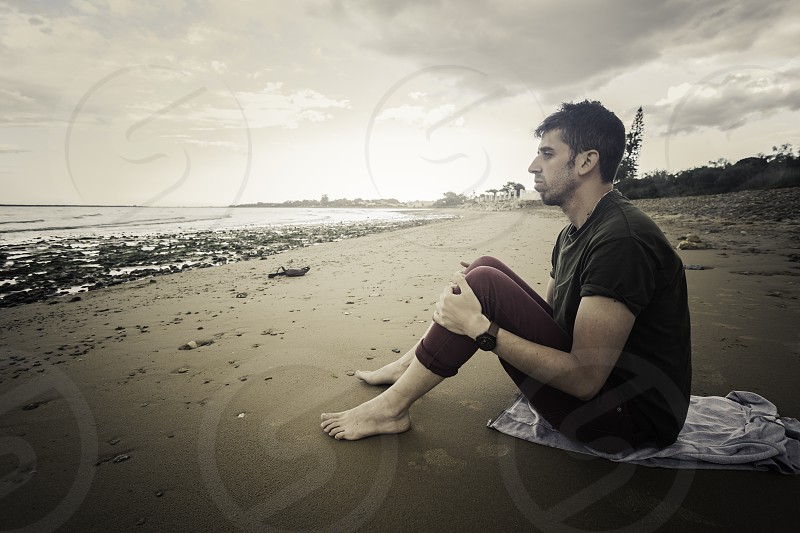Young adult sitting barefoot on the seashore photo