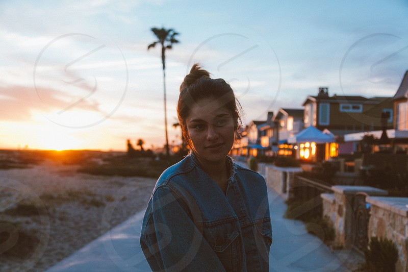 woman in blue denim jacket by the street during sunset photo