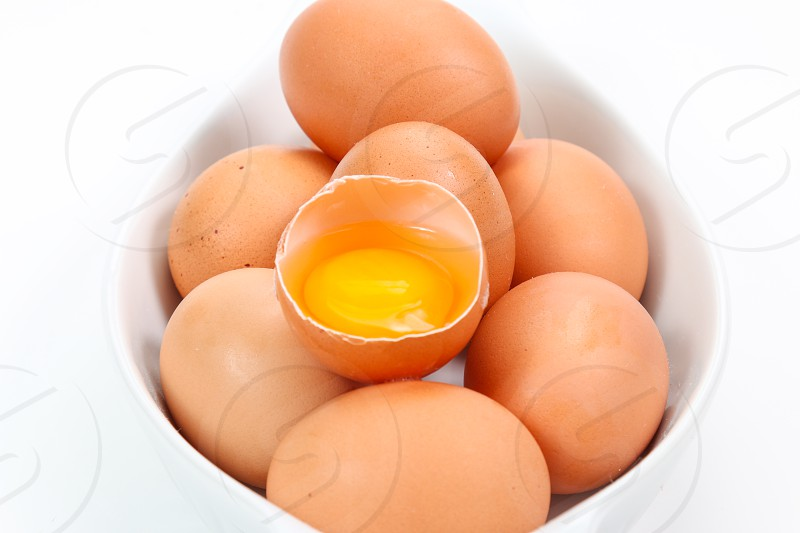 Raw eggs on white background with one egg crack photo