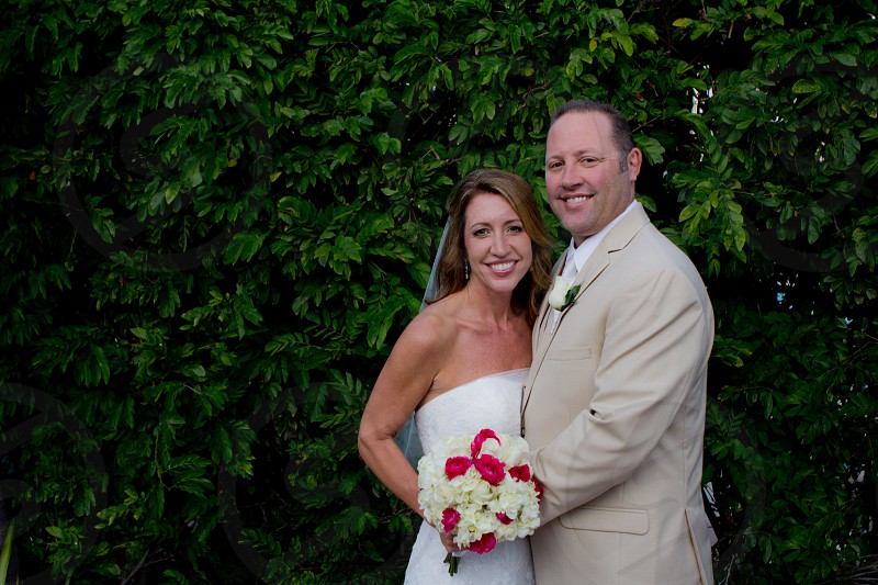 newlyweds standing in front green hedge during daytime photo