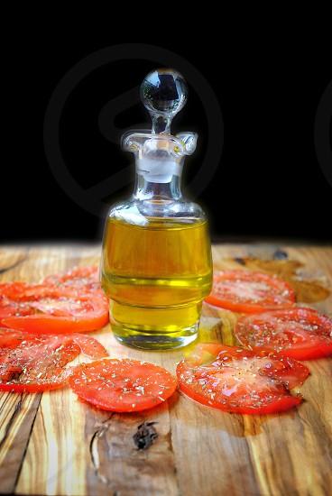 slice tomato beside yellow bottled liquid photo